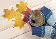 Woman holding a cup of coffee on the autumn background. Royalty Free Stock Image