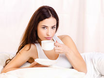 Woman holding cup of coffee in bed Royalty Free Stock Photography