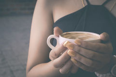 Woman holding cup of coffee in coffee shop. Made vintage-retro style background Royalty Free Stock Photo