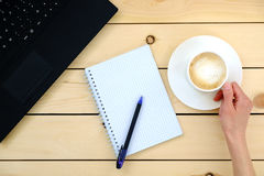 Woman holding a cup of coffee. Empty blank, pen, laptop. Stock Photo