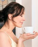 Woman holding a cup of coffee in the kitchen Stock Photography