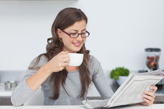 Woman holding a cup of coffee and reading a newspaper Royalty Free Stock Images