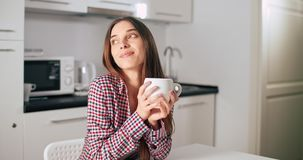 Woman Enjoy Coffee Aroma. Woman holding cup of coffee while sitting in the kitchen, indoors morning time shot stock footage
