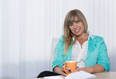 Woman is holding a cup of coffee Royalty Free Stock Images