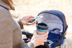 Woman holding cup of coffee to go and using smartphone during walk with baby carriage. Modern young business woman stock images