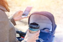 Woman holding cup of coffee to go and using smartphone during walk with baby carriage. Modern young business woman royalty free stock photo