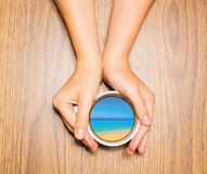 Woman holding cup with dream about tropical vacation. Against wooden table. Top view. Conceptual photo. Collage Royalty Free Stock Image