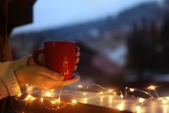 Woman holding cup of hot beverage on balcony decorated with Christmas lights, closeup with space for text. Winter evening royalty free stock photography
