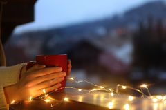 Woman holding cup of hot beverage on balcony decorated with Christmas lights, closeup with space for text royalty free stock images