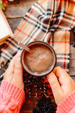 Woman holding cup of hot chocolate. Hot Chocolate in wooden tabl Royalty Free Stock Images