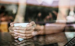 Woman holding a cup of hot coffee in cafe near window Royalty Free Stock Photography