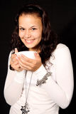 Woman holding cup with hot tea. Young woman smiling and holding a cup with hot coffee on black background Royalty Free Stock Photos