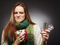 Woman holding a cup of hot tea and expressing disgust to some bl. Studio shot of a woman holding a cup of hot tea and expressing disgust to some blister packed Royalty Free Stock Photography