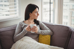 Woman holding cup while looking through window. At home Royalty Free Stock Images