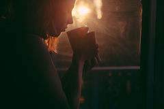 Woman Holding Cup Near Window Reflected With Sun Royalty Free Stock Photos