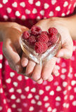 Woman holding a cup of raspberries Royalty Free Stock Image