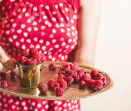 Woman holding a cup of raspberries Stock Image