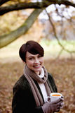 A woman holding a cup of soup in autumn time Royalty Free Stock Photography