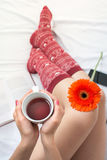 Woman holding a cup of tea in bed Stock Photos