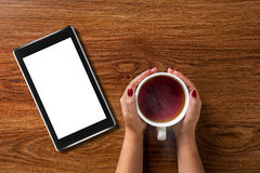 Woman holding cup of tea with tablet pc on wood Royalty Free Stock Images