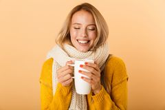 Woman holding cup of tea wearing scarf posing isolated over yellow wall background. Photo of a cute pretty woman holding cup of tea wearing scarf posing isolated royalty free stock images