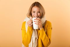 Woman holding cup of tea wearing scarf posing isolated over yellow wall background. Photo of a cute pretty woman holding cup of tea wearing scarf posing isolated stock photos