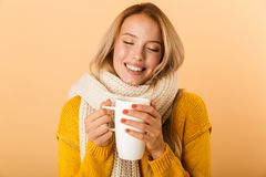 Woman holding cup of tea wearing scarf posing isolated over yellow wall background. Photo of a cute pretty woman holding cup of tea wearing scarf posing isolated royalty free stock image