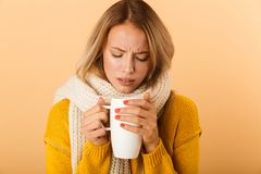Woman holding cup of tea wearing scarf posing isolated over yellow wall background. Photo of a displeased woman holding cup of tea wearing scarf posing isolated royalty free stock image
