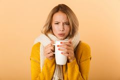Woman holding cup of tea wearing scarf posing isolated over yellow wall background. Photo of a displeased woman holding cup of tea wearing scarf posing isolated stock images