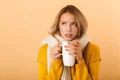 Woman holding cup of tea wearing scarf posing isolated over yellow wall background. Photo of a displeased woman holding cup of tea wearing scarf posing isolated stock image