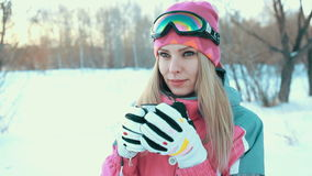 Woman holding cup from thermos in hands and drink tea at snowy branches of winter trees background. Woman holding cup from thermos in hands at snowy branches of stock video footage