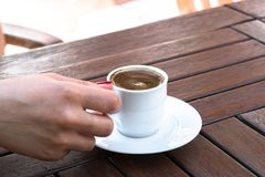 A Woman Holding a Cup of Turkish Coffee. On a Wooden Table Royalty Free Stock Photos