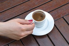 A Woman Holding a Cup of Turkish Coffee. On a Wooden Table Royalty Free Stock Photography