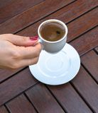 A Woman Holding a Cup of Turkish Coffee. On a Wooden Table Stock Image