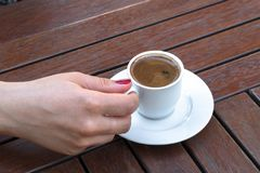 A Woman Holding a Cup of Turkish Coffee. On a Wooden Table Royalty Free Stock Images