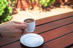A Woman Holding a Cup of Turkish Coffee. On a Wooden Table Stock Photos