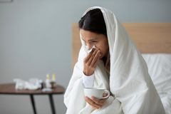 Free Woman Holding Cup With Hot Beverage And Blows Runny Nose Royalty Free Stock Photos - 164857578