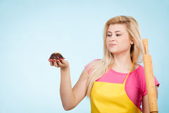 Woman holding cupcake and rolling pin wearing apron Royalty Free Stock Photos