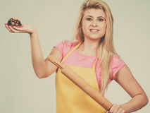 Woman holding cupcake and rolling pin wearing apron Royalty Free Stock Photography