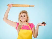Woman holding cupcake and rolling pin wearing apron Stock Images