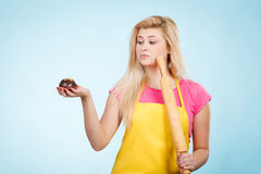 Woman holding cupcake and rolling pin wearing apron Stock Photography