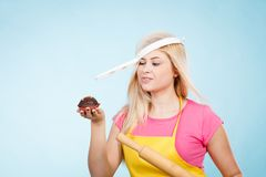 Woman holding cupcake, rolling pin wearing colander on head Royalty Free Stock Photos