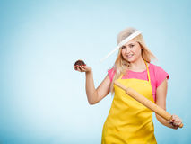 Woman holding cupcake, rolling pin wearing colander on head Royalty Free Stock Image