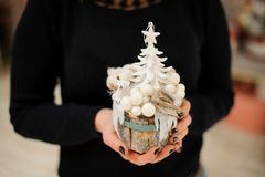 Woman holding a cute Christmas composition made of white toy tree, bear and balls on the fir tree stump. Woman holding a cute Christmas composition made of white royalty free stock image