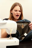 Woman holding damaged jeans and looking shocked. Because of a hole Royalty Free Stock Photography