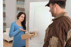Woman holding damaged package from delivery man Royalty Free Stock Photos