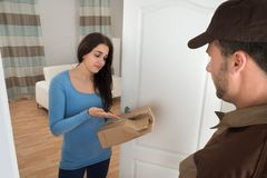 Woman holding damaged package from delivery man Royalty Free Stock Photography