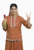 Woman holding a Dandiya at Navratri and making victory sign Stock Photos