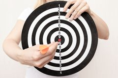 Woman holding a dart board and darts in hands close up, aiming and targetting in business and life concept royalty free stock photography