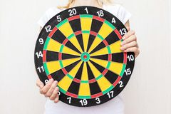 Woman holding a dart board in hands close up, aiming and targetting concept stock photography